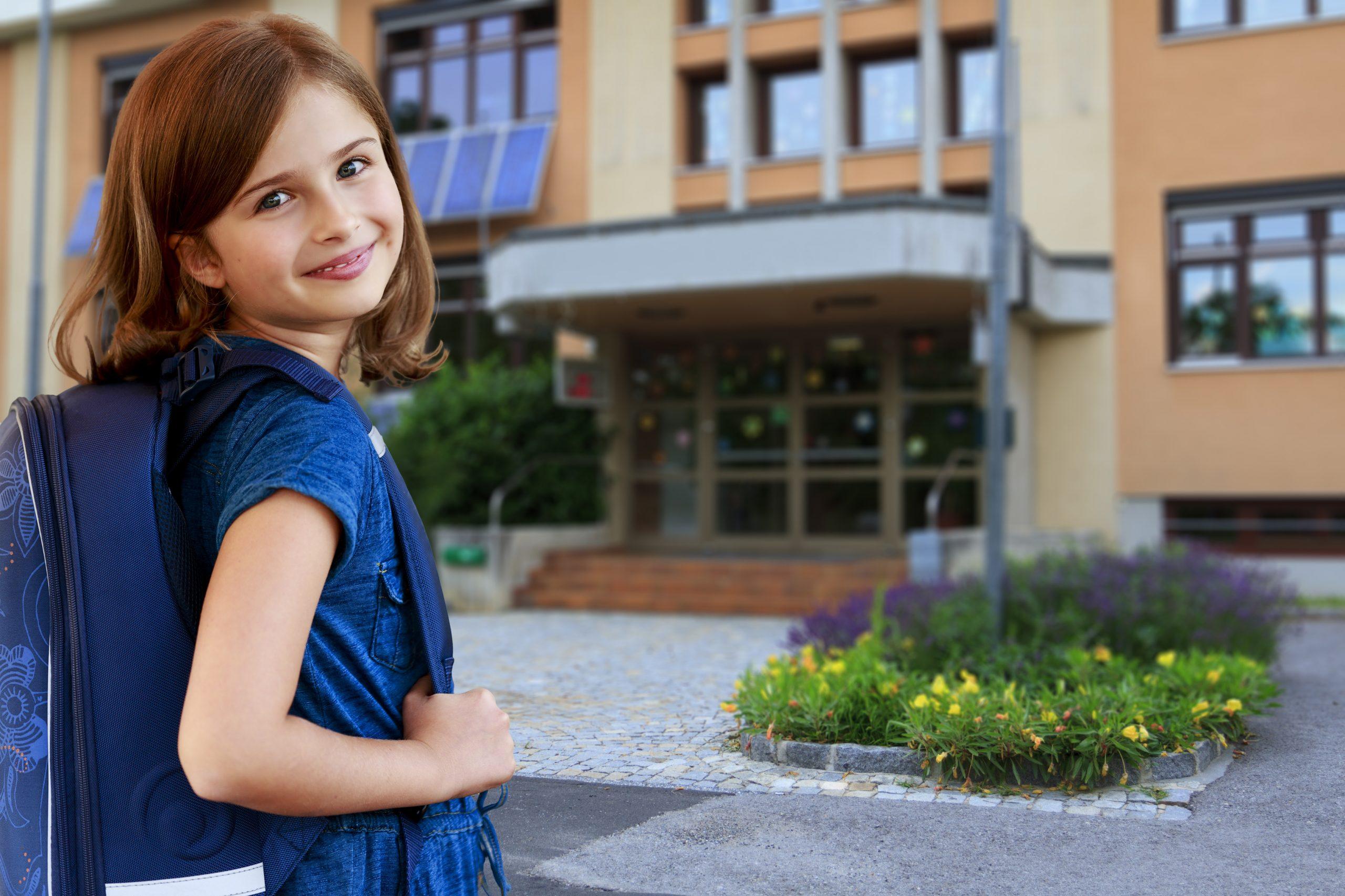 Mädchen vor Schule groß